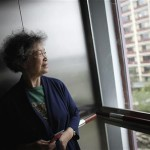 Yuefeng stands in elevator of her apartment building at Cherish Yearn care center facility in Shanghai